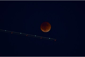 Blood Moon with airplane trails
