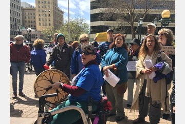 Oakland #MarchForOurLives MarchforOurLives Choral Majority singing.  Two women in the center one standing singing and the other sitting in her walker plays a flat skin drum.  Around them other singers singing. I ain't' gonna let gun violence turn me arou
