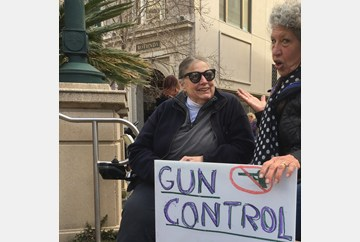 Oakland March for our Lives two older women in wheelchairs holding a sign that reads Gun Control = Right to Life. #MarchForOurLives