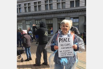 Oakland March for Life Elder Woman standing holding a sign that reads Peace No Guns Anywhere We Elders Stand With These kids! #MarchForOurLives