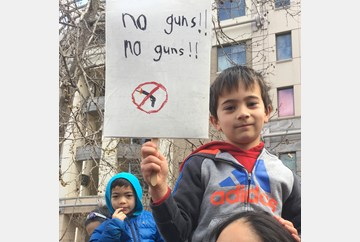 Oakland March for our lives.  Young child on mothers shoulders holding a sign he made that reads No Guns! No Guns!  #MarchForOurLives