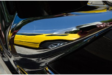 A yellow Mustang reflected in the chrome wheel of another. Shot at the Ford Mustang show held in Smithfield VA 12 May
