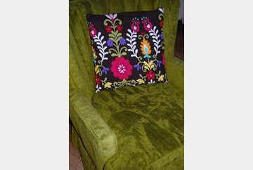 Pillow made from the shower curtain sitting on a funky retro green chair, also from Goodwill!