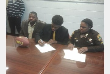 Flanked by his parents, Heritage's Khalid Abdullah signs with james Madison